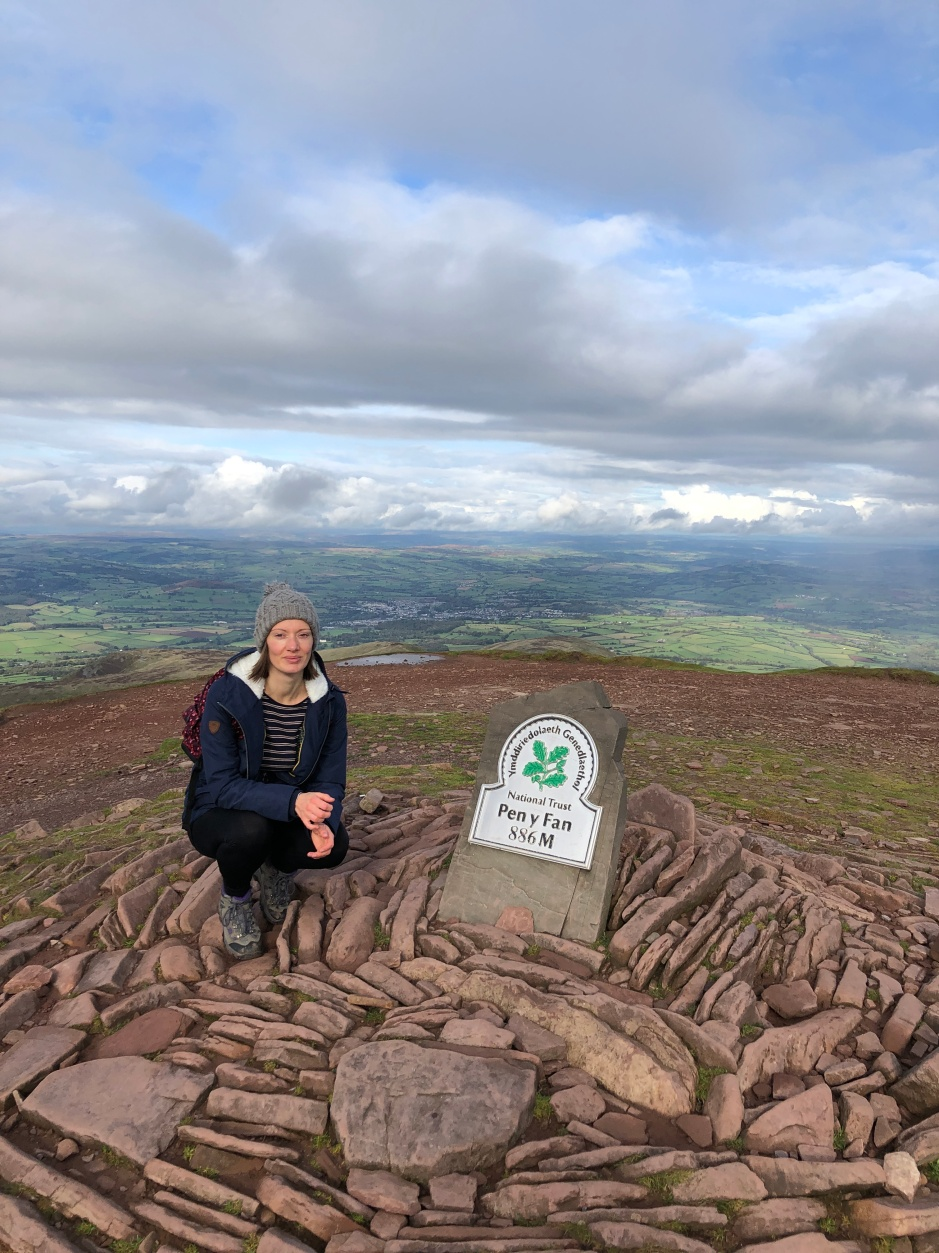 female hiker victoria sully next to Pen Y Fan summit peak 886m marker