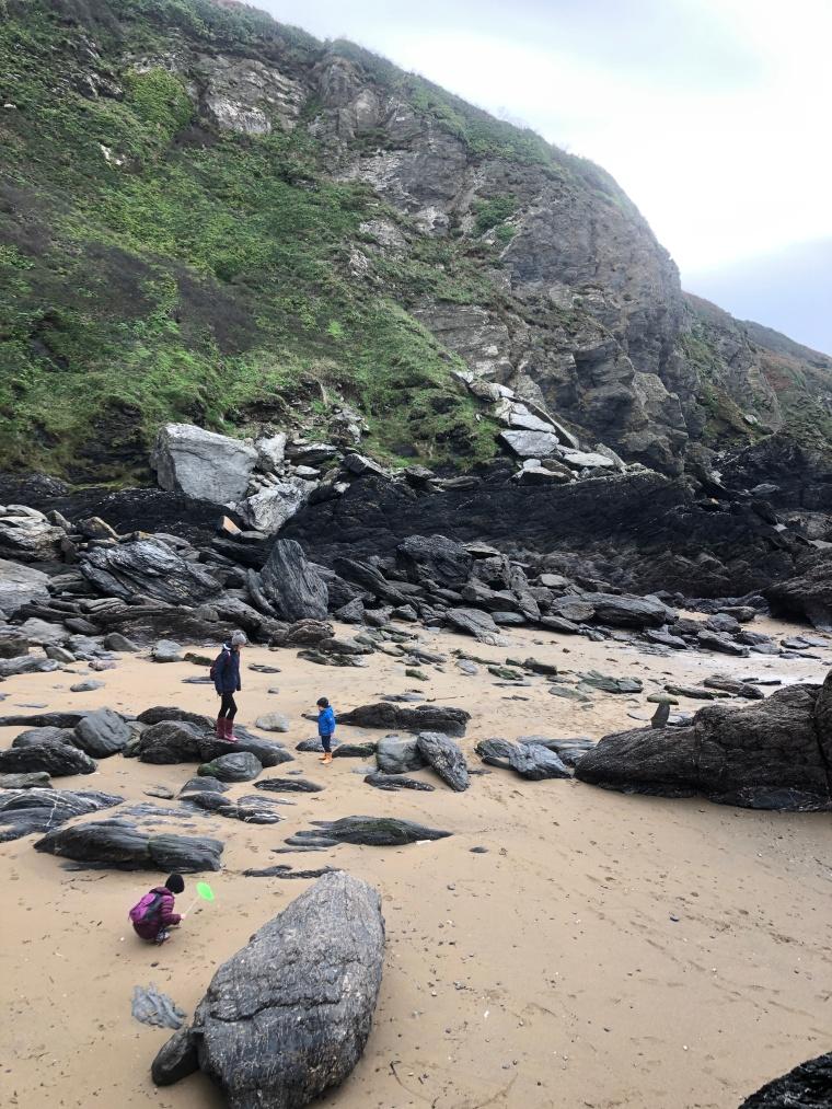 Cornwall with kids: Hemmick Beach - mum and two children exploring rocks on beach