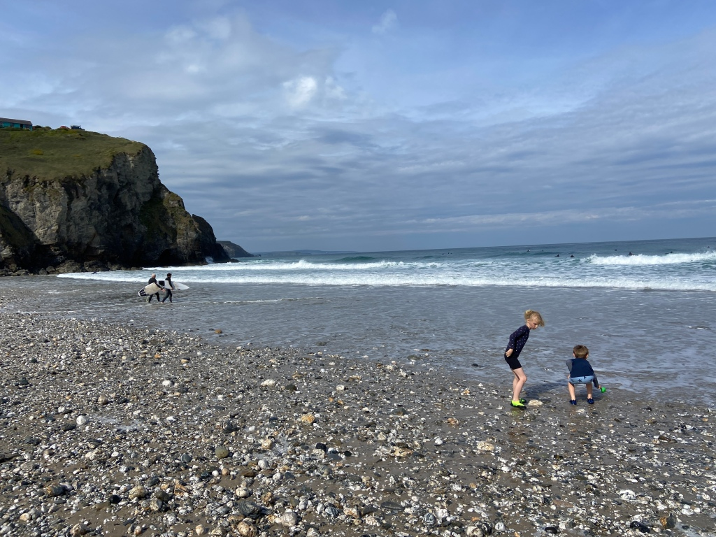 6 year old and 9 year old playing in the sea on a rocky pebble beach at Porthtowan beach in Cornwall with surfers in the background