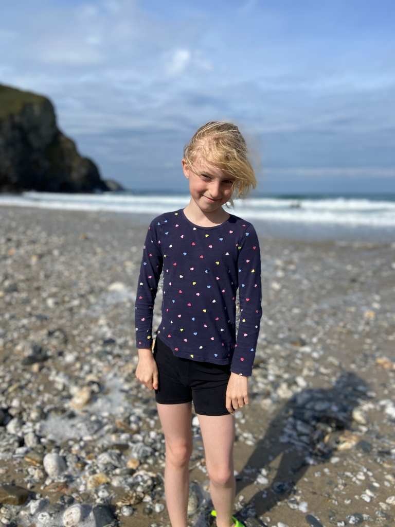 My 9 year old daughter smiling for a portrait photo at Porthtowan beach in Cornwall