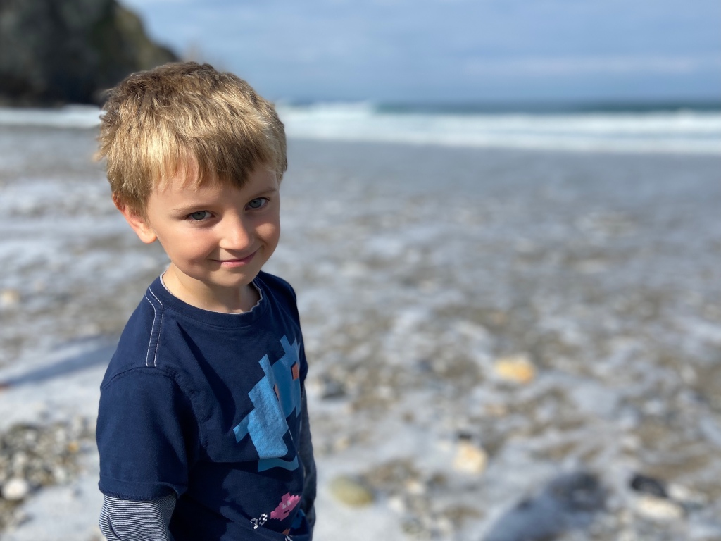 My 6 year old son smiling for a portrait photo at Porthtowan beach in Cornwall