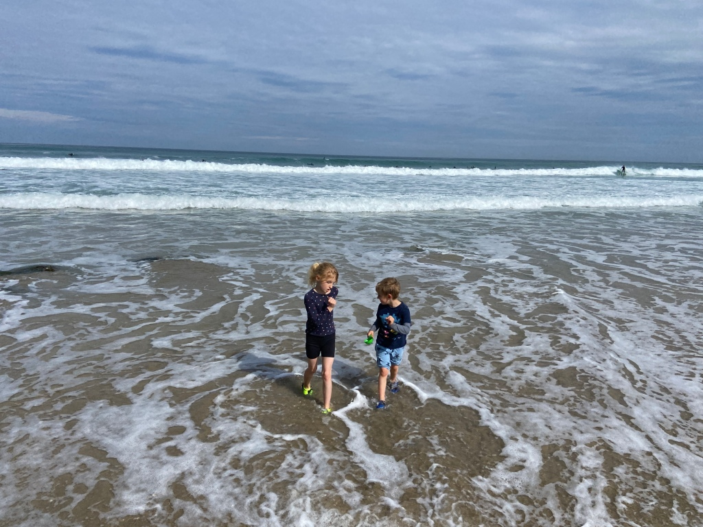 my two children running away from the sea in the shallow water playing at Porthtowan beach in Cornwall