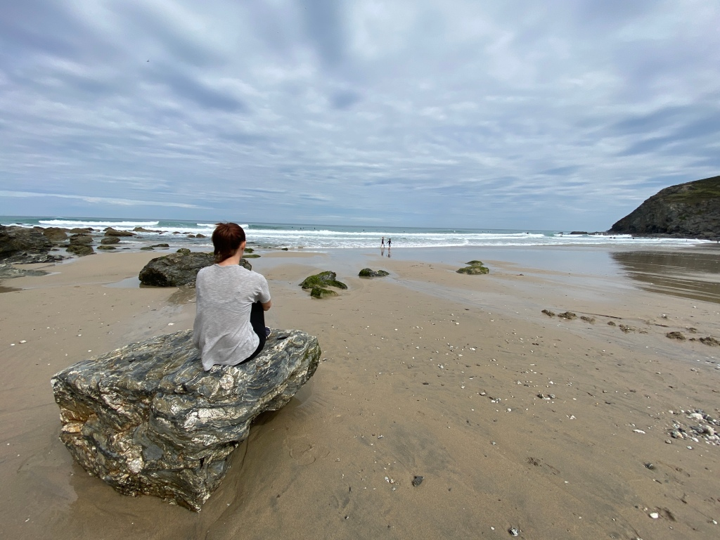 Me sat on a rock looking out to sea and watching my children splash in the sea at Porthtowan beach in Cornwall