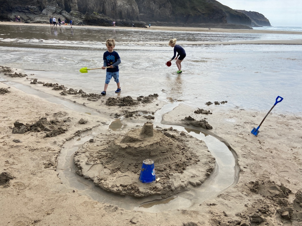 Kids playing in water and making sandcastles at Perranporth beach in Cornwall