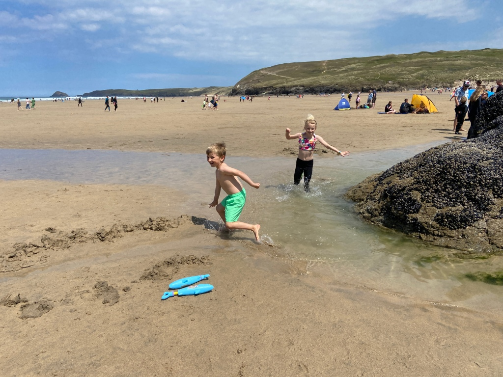 Kids splashing in the pools of water on the beach at Perranporth beach in Cornwall