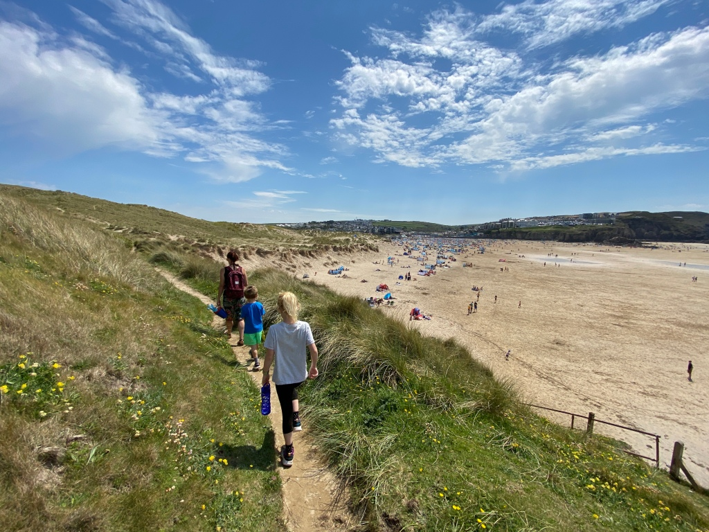 Family walking along the sand dunes at Perranporth beach in Cornwall