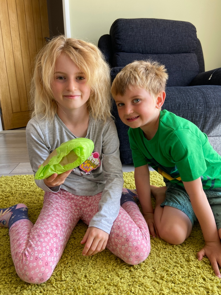 siblings smiling for the camera holding a birthday present