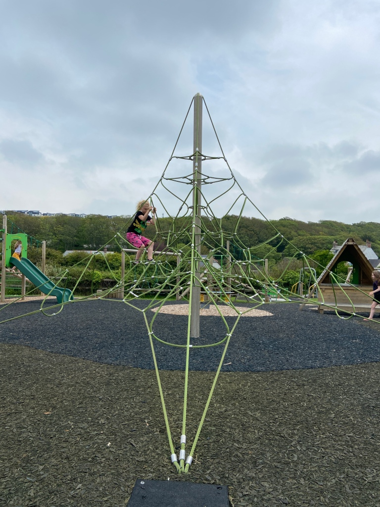 Girl climbing a climbing frame at a play park in Perranporth in Cornwall