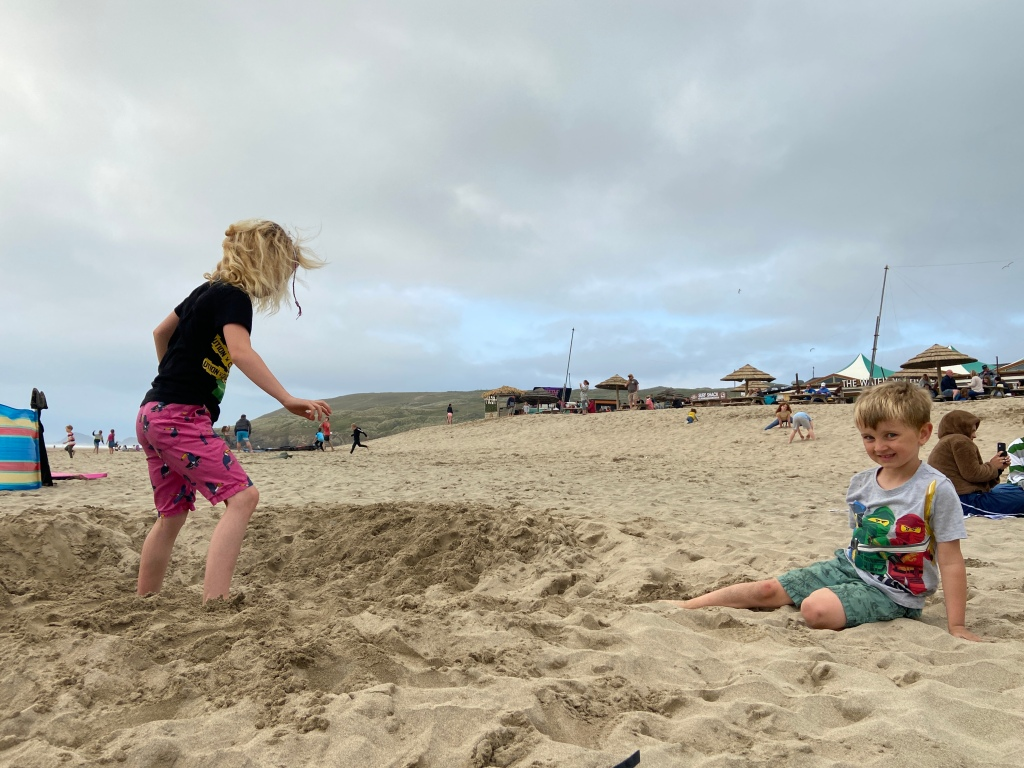 Kids playing with sand at Perranporth beach in Cornwall
