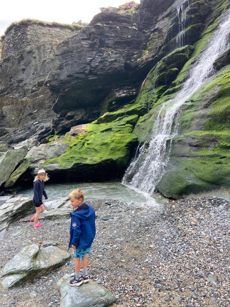 waterfall running down cliffs to beach at Tintagel beach in Cornwall