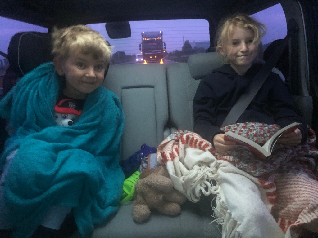 Kids in Bongo campervan off on holiday on the motorway, wrapped in blankets as it's 5am