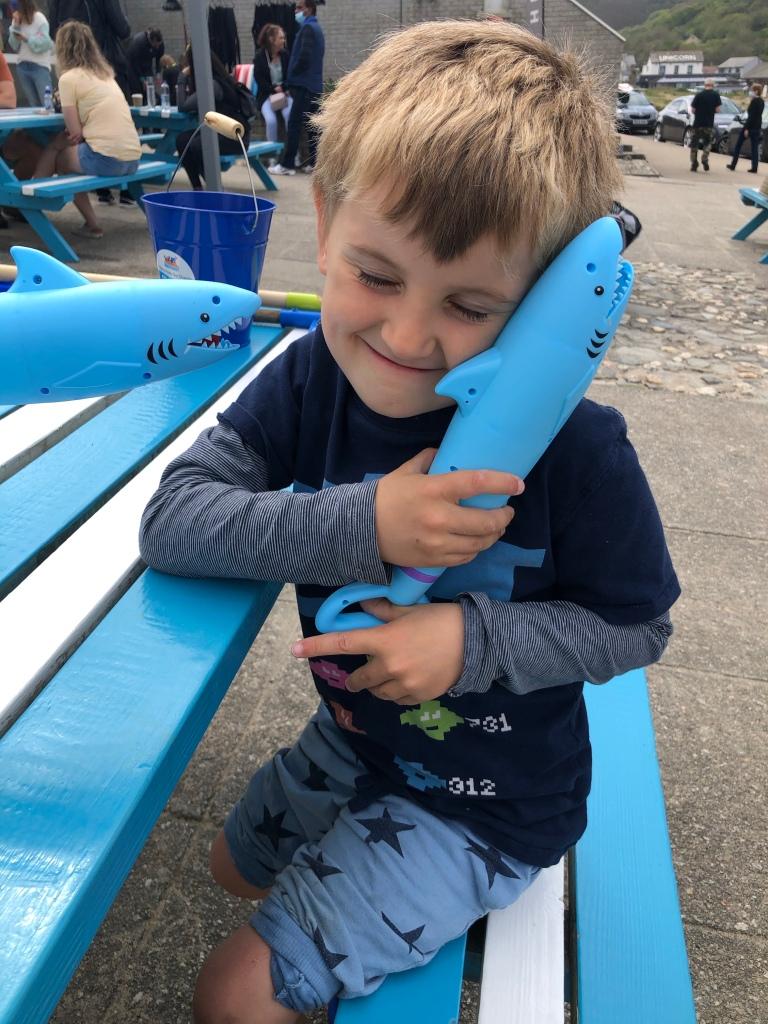 My six year old reuben hugging a shark shaped water pistol at Porthtowan beach in Cornwall