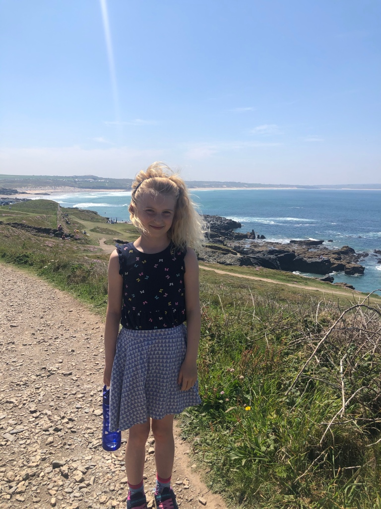 Smiling girl with large sea view behind near Godrevy lighthouse in Cornwall