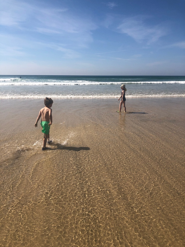Kids splashing in shallow waves at The Towans beach in Cornwall