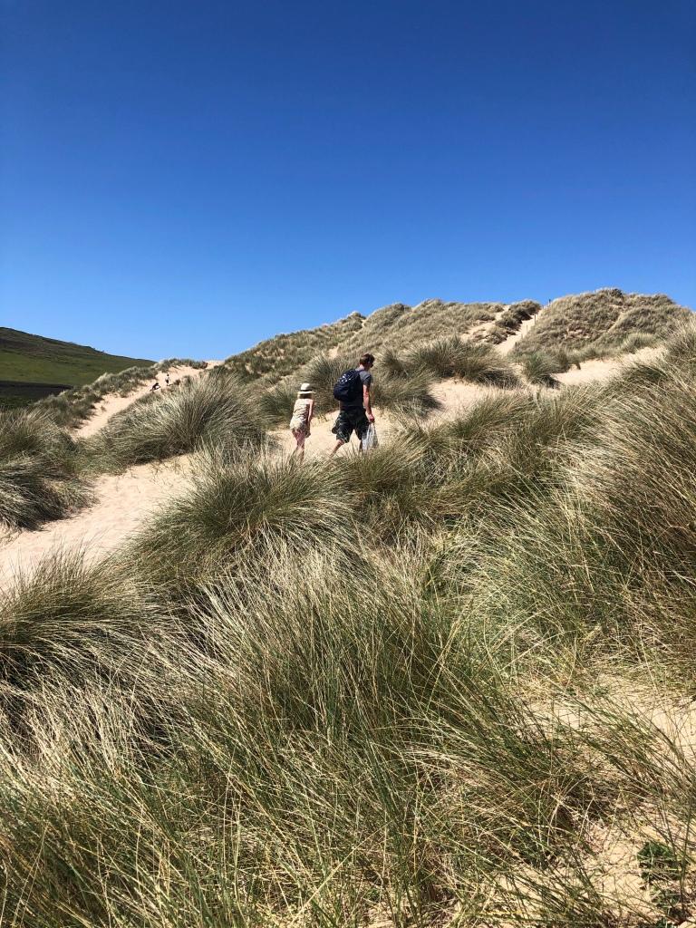 walking up sand dunes Hollywell beach near newquay cornwall