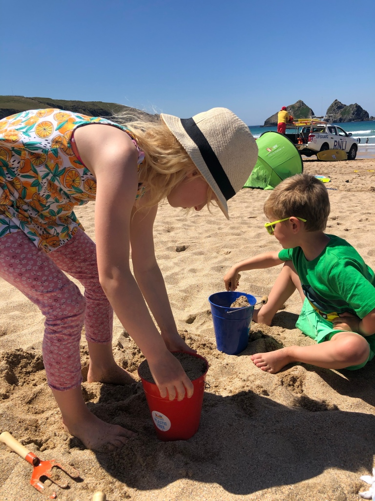 kids having fun filling buckets with sand at Hollywell beach near newquay cornwall