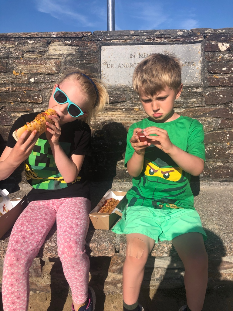Kids sat on a bench eating vegan hotdogs in Perranporth