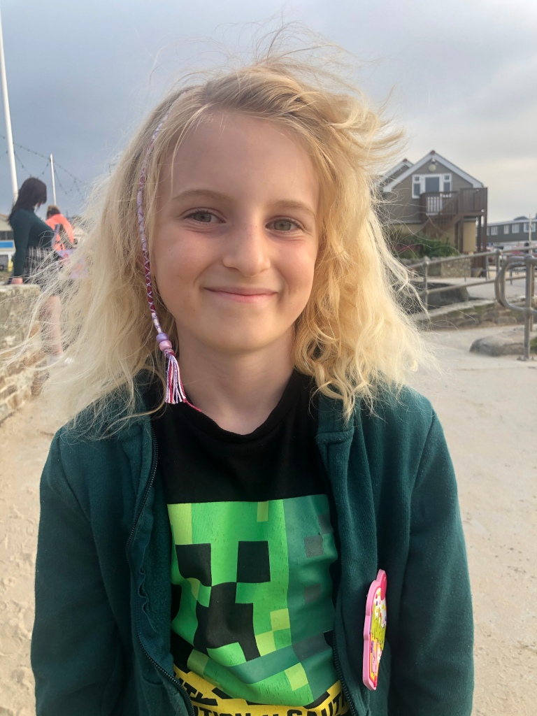 Smiling girl with hair wrap braid in Perranporth in Cornwall